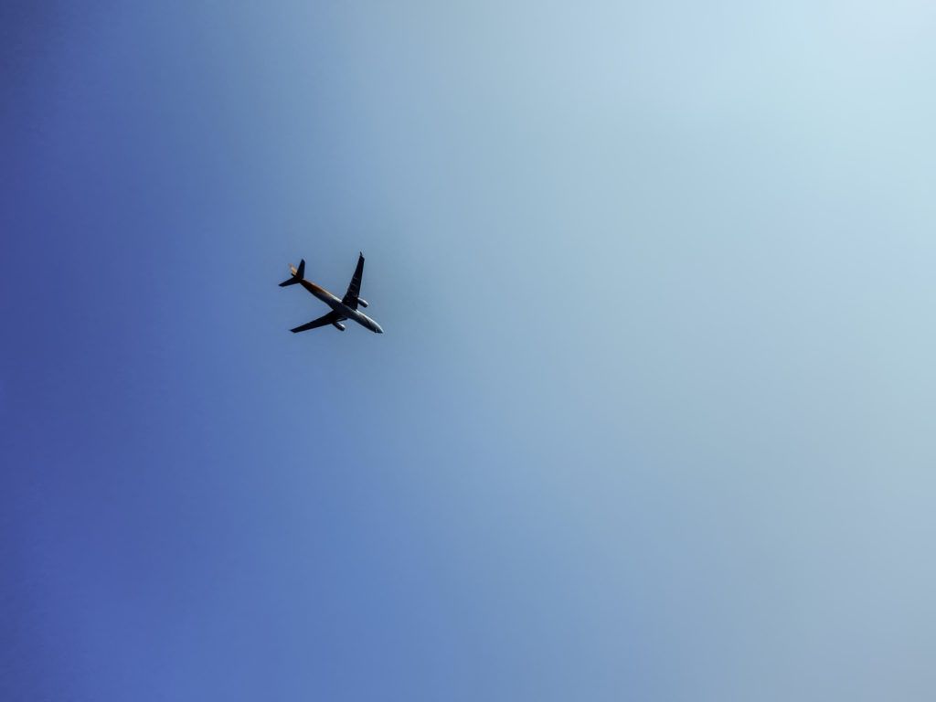 快晴の空を飛ぶ飛行機