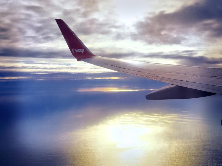 夕暮れの海の上を飛ぶ飛行機