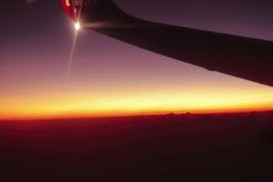 夕暮れの空の上を飛ぶ飛行機
