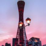 ピンクの夕焼けの中のポートタワーと街灯