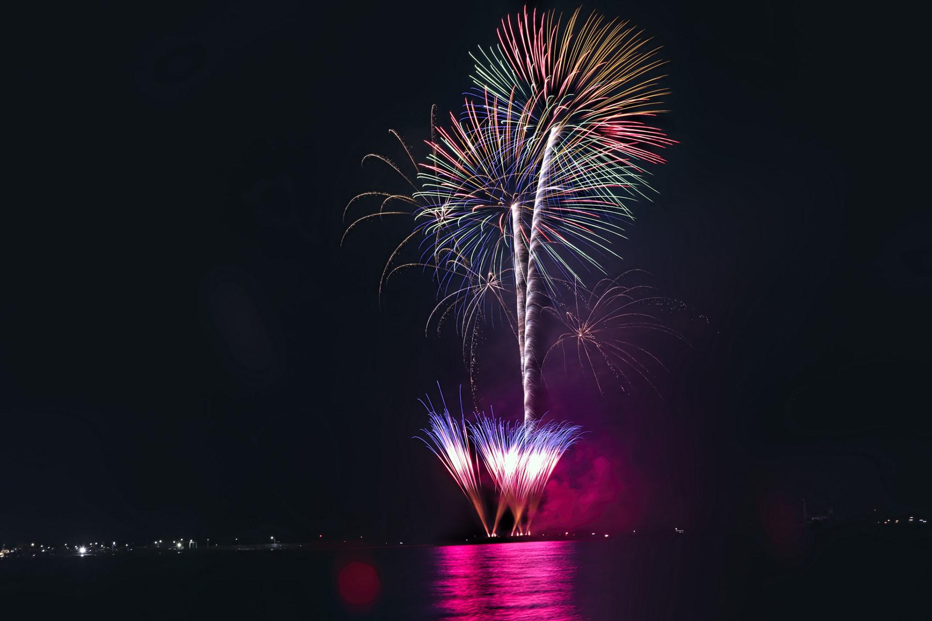 赤い光が水面に反射する色鮮やかな花火