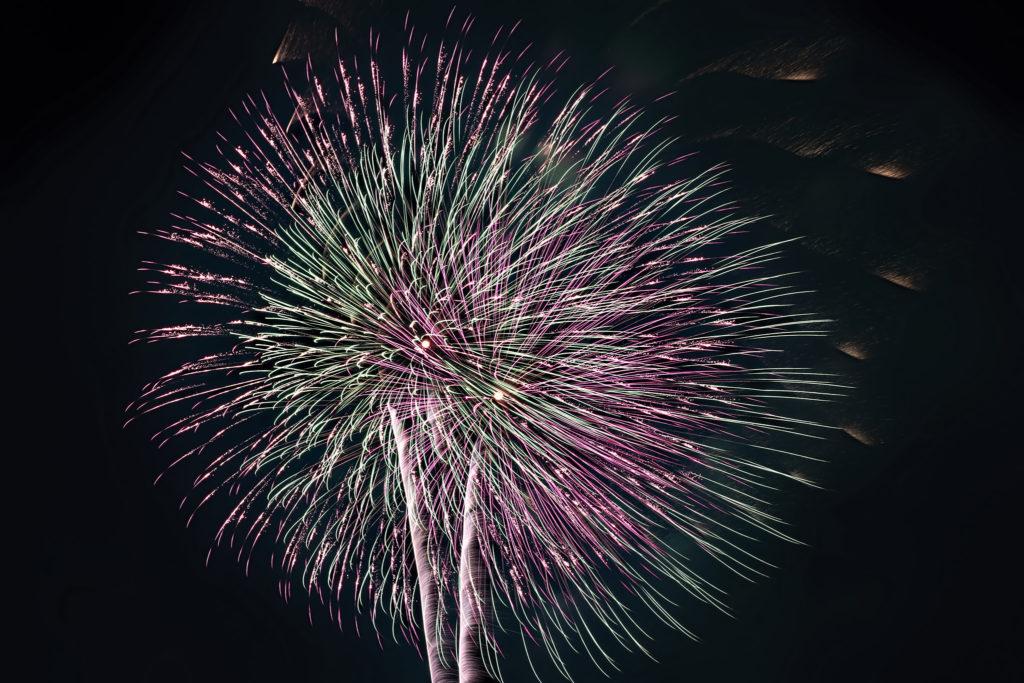夏の夜空を彩るピンクと緑の大輪の花火
