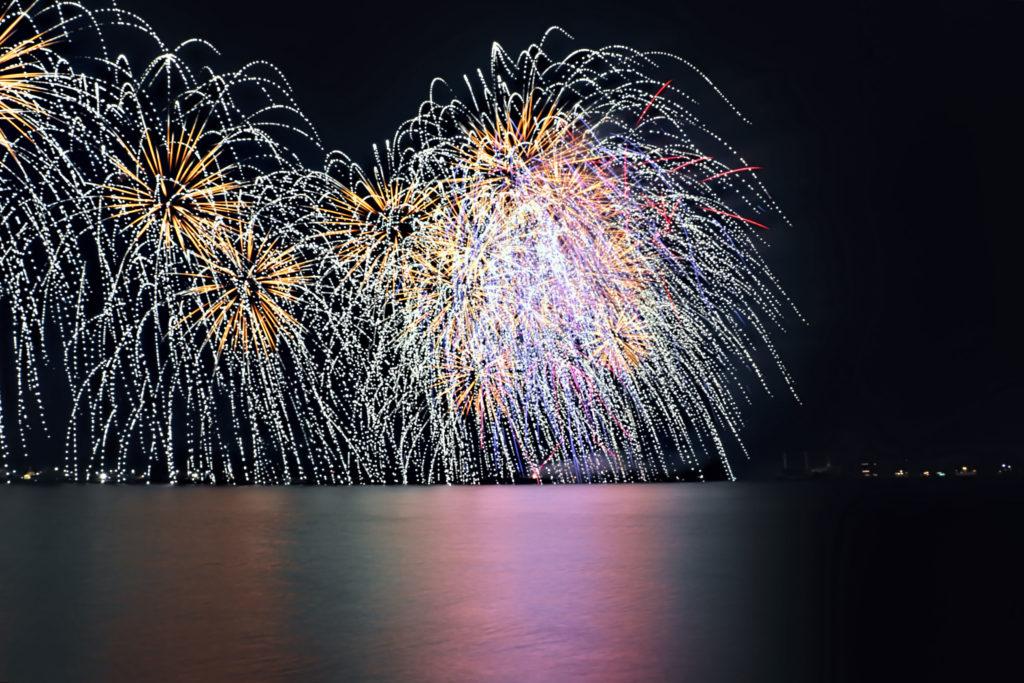 海面に垂れ落ちる色鮮やかな花火