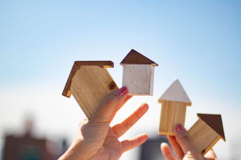 ベランダで家の積み木を持つ両手