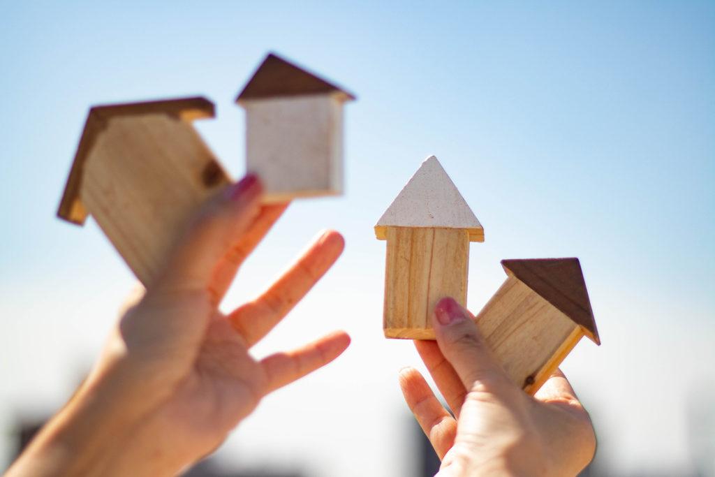 空に向かって家の積み木を掲げる手